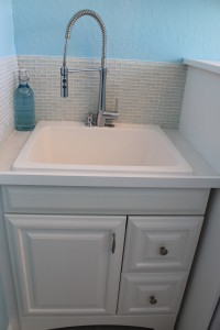 Laundry sink with faucet and tile backsplash.
