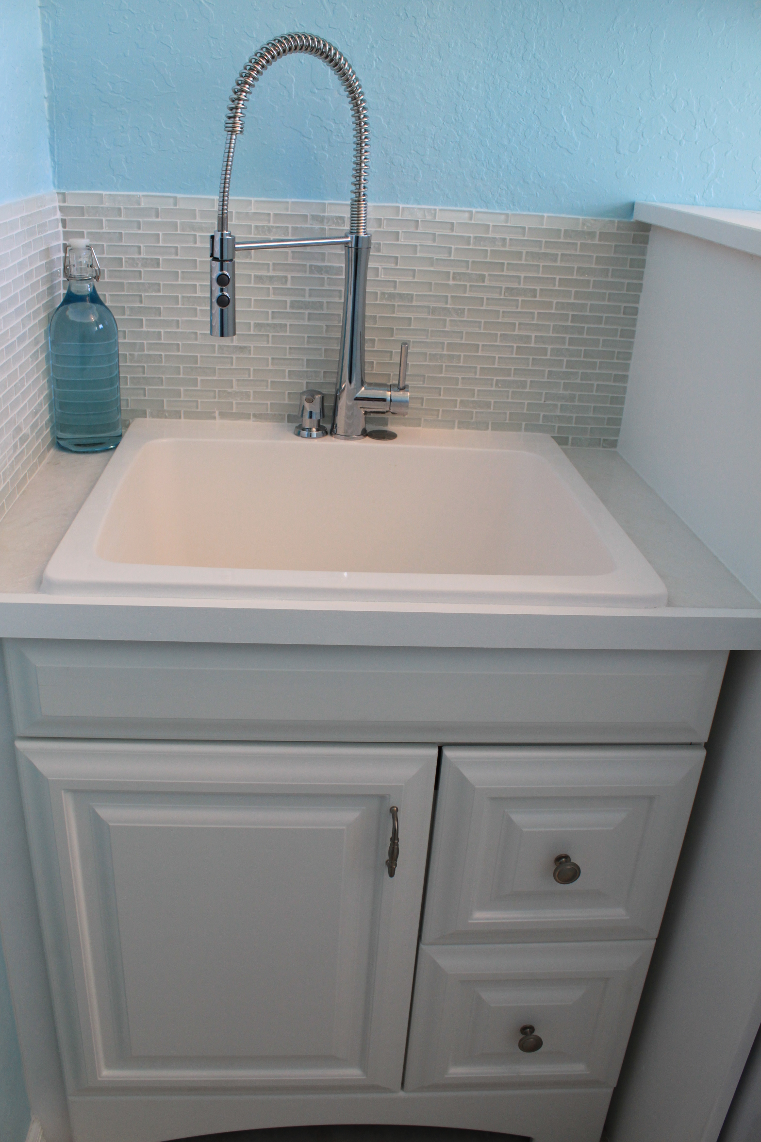 laundry sink with faucet and tile backsplash